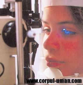 Pacienta este tratată ambulatoriu pentru o problemă oftalmologică şi i-a fost fixat capul pentru a împiedica mişcarea Iul. Medicul foloseşte un aparat cu laser pentri tratarea retinei. Laserul este transmis sub forma unei serii de pulsuri.